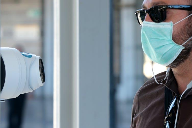رجل يرتدي قناعا له درجة حرارة مأخوذة بكاميرا حرارية في أثينا.
